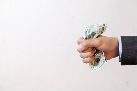 squeezing: Businessman squeezing bank notes in white isolated Stock Photo
