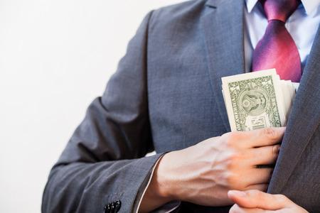 ビジネスの男性 - 腐敗と不正行為概念の上着のポケットにお金を隠して