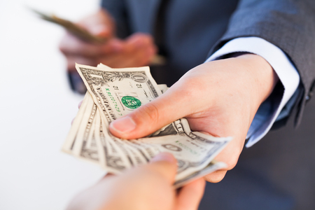 depravity: Business man giving bank notes to another person. Corruption and Payment concept Stock Photo