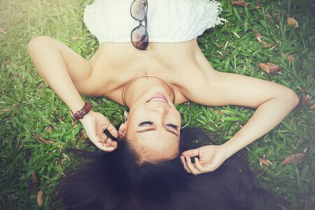 woman laying down: Young happy and smiling woman laying down on green grass - happiness concept
