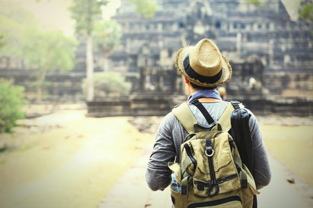siem reap: Young traveler wearing a hat with backpack and tripod - at Angkor Wat, Siem Reap, Cambodia