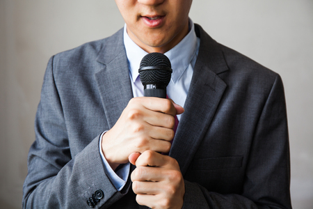 low self esteem: Young talking man holding microphone without confidence on isolated white background