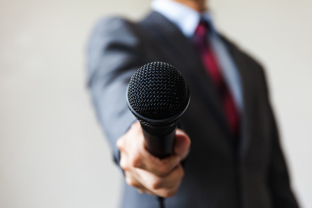 spokesperson: Man in business suit holding a microphone conducting a business interview, journalist reporting, public speaking, press conference, MC