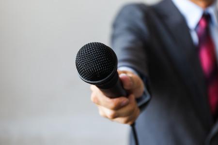 業を行なうマイクを持っているビジネス スーツを着た男のインタビュー、ジャーナリストのレポート、人前で話す、プレスカンファレンス、MC