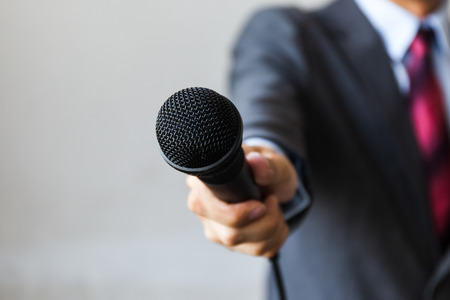 L'uomo vestito di affari in possesso di un microfono condurre il colloquio di lavoro, report giornalista, parlare in pubblico, conferenza stampa, MC Archivio Fotografico