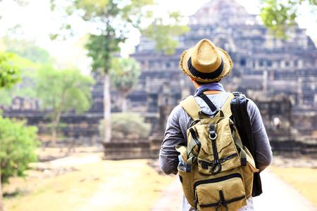 アンコール ワット、シェムリ アップ、カンボジアではバックパックと三脚 - 帽子をかぶって若い旅行者