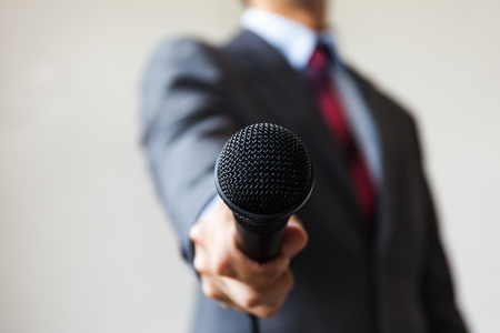 mc: Man in business suit holding a microphone conducting a business interview, journalist reporting, public speaking, press conference, MC