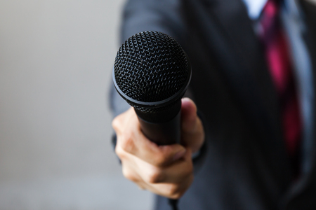 El hombre en traje de negocios que sostiene un micrófono realización de una entrevista de negocios, informes periodista, hablar en público, rueda de prensa, MC Foto de archivo