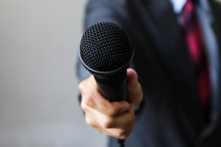 reportero: El hombre en traje de negocios que sostiene un micrófono realización de una entrevista de negocios, informes periodista, hablar en público, rueda de prensa, MC