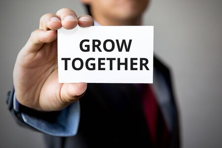 growing partnership: Businessman presenting Grow Together word on white card.