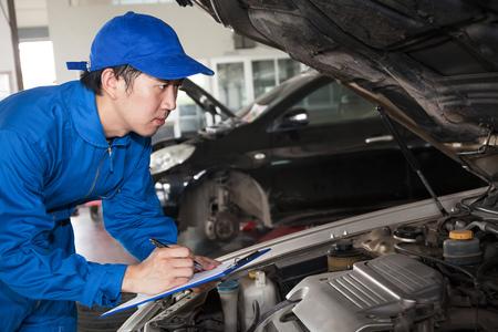車のメンテナンスのため修復する青い技術者制服に男。