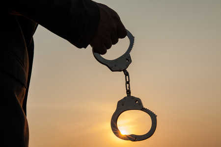 abolition: Business Man holding handcuffs after releasing over sunset background. Freedom and Burden-free concept