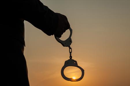 ビジネスを抱きかかえたは、夕日を背景に解放した後手錠します。自由と無料の負担の概念 写真素材