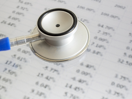 selectively: Stethoscope on financial data - indicates to check and diagnose about finance (selectively focus on stethoscope, blurred out the data) Stock Photo