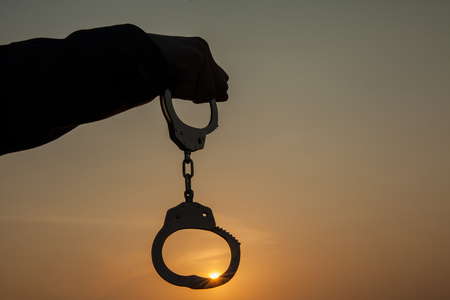 redemption: Business Man holding handcuffs after releasing over sunset background. Freedom and Burden-free concept