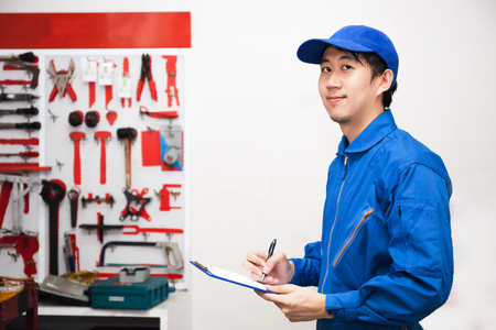 Young male engineer at work in mechanic tools storage room. Stockfoto