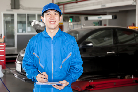 valeting: Asian car technician smiling in garage service.