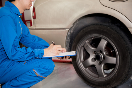 automotive technician: Young automotive technician checking on car tires in garage. Stock Photo