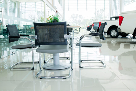 Inside car showroom interior with group of chairs and table for discussion.