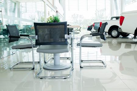 Interior de exposición de automóviles en el interior con el grupo de sillas y mesa para su discusión. Foto de archivo