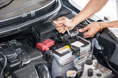 Mechanische ingenieur die auto-batterij in de garage bevestigt (selectieve focus). Stockfoto