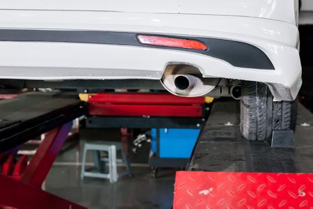 Car muffler in process of being modified in garage.