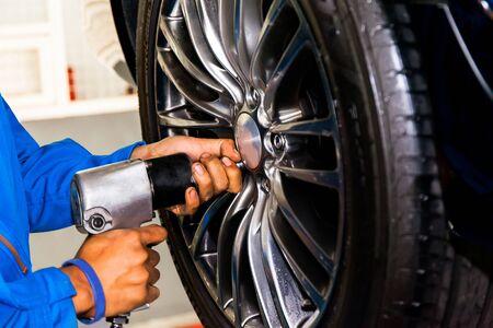 unscrewing: mechanic screwing or unscrewing car wheel at car service garage