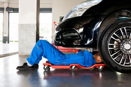 Mecánico en el uniforme azul que se acuesta y que trabaja bajo el coche en el garaje de un servicio de automóviles Foto de archivo
