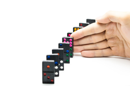 intervention: Businessman hand stopping domino effect on isolated white background with copy space - business solution, strategy and successful intervention concept