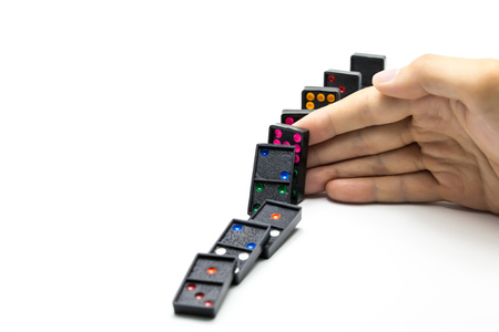 intervene: Businessman hand stopping domino effect on isolated white background with copy space - business solution, strategy and successful intervention concept