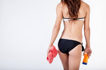 sun screen: Back of walking woman in bikini holding sandals and sun screen lotion in white isolated background.