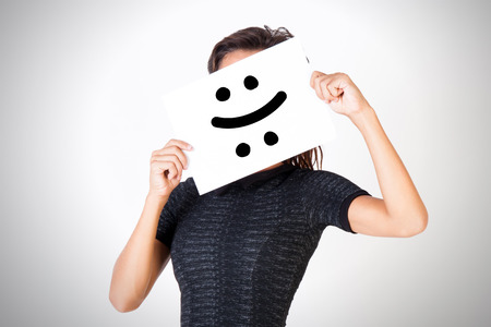 Young woman facing bipolar disorder - happy and sad two-faced expression Stock Photo