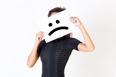 dissatisfied: Woman in elegant dress holding dissatisfied face paper - unhappy and dissatisfied treatment concept Stock Photo