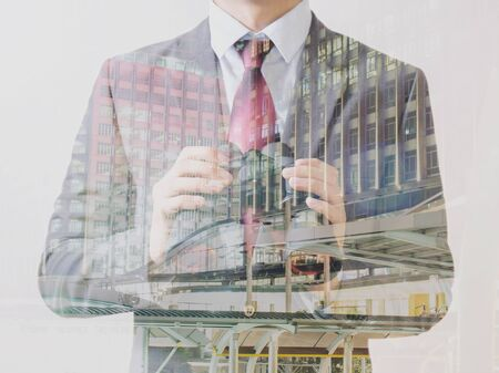double the chances: Double Exposure of Businessman in suit with skyscraper on the background Stock Photo
