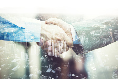 Double Exposure of Businessmen in suit handshaking agreed upon partnership. Stock Photo