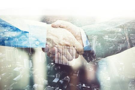 Double Exposure von Geschäftsmänner in Anzug Handshaking auf Partnerschaft vereinbart.