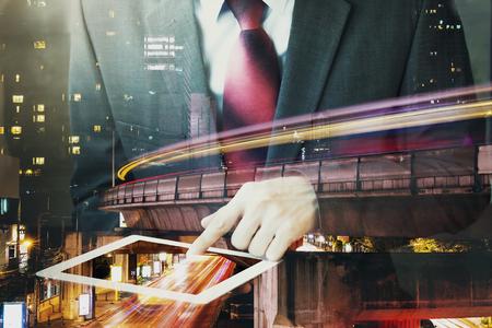 二重露出の実業家長時間露光都市場面でタブレットに触れます。