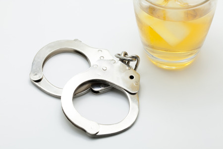 responsibly: Glass of whiskey and handcuffs - Drinking law concept. Stock Photo
