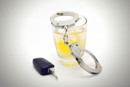 under the influence: Car key with glass of whiskey and handcuffs - drive under influence concept.
