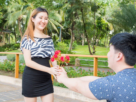 Asian man kneels down giving his girlfriend a bunch of roses.