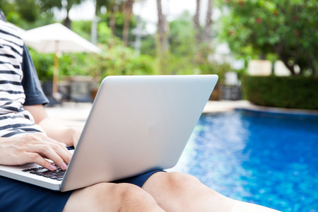 anywhere: Man using a laptop in the pool on vacation - work anywhere and internet work concept