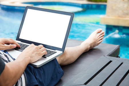 nomad: Screen mockup of laptop that a man is using in the pool on vacation - work anywhere and internet work concept