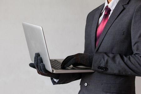 man searching: Business man wearing gloves and using computer - fraud, hacker, theft, cyber crime concept