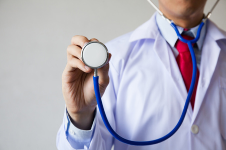 consulta médica: Primer plano de médico de sexo masculino que usa el estetoscopio y centrarse en el estetoscopio