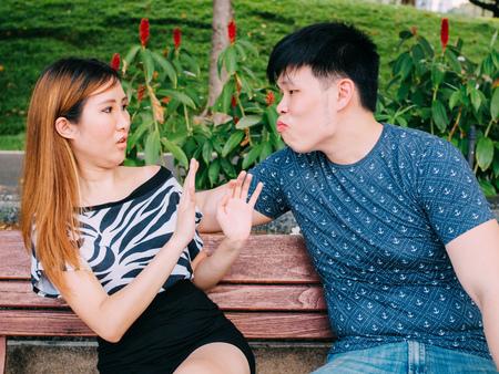 アジア系の若い男は女の子にキスしようとして拒否されます。 写真素材
