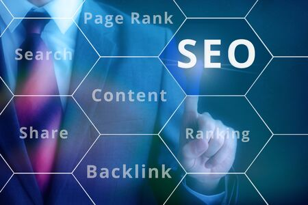 page rank: Businessman pressing SEO button on virtual touch screen on blue technology background Stock Photo