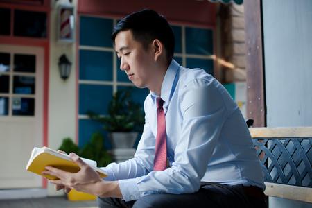 personas pensando: Hombre asiático que lee un libro que se sienta en banco