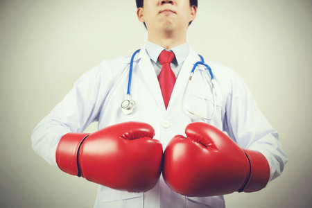 guarding: Asian Doctor wearing boxing gloves in white background - guarding diseases and sickness concept