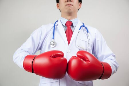 Hospital care: Asian Doctor wearing boxing gloves in white background - guarding diseases and sickness concept