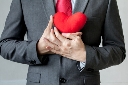 Kaufmann zeigt Mitgefühl in seinem Anzug rotes Herz auf der Brust halten - crm, Service Geist-Business-Konzept